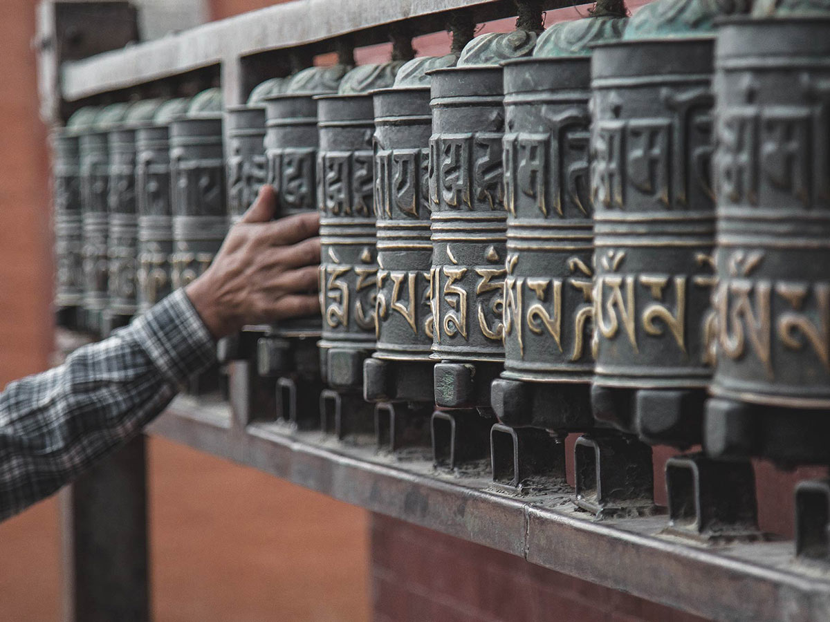 Image of person holding on black railing with sanskrit letters
